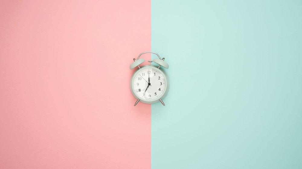 Wecker auf blauen und rosa Hintergrund